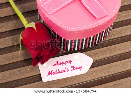 Red rose bud heart shaped pink gift box and mothers day card - stock photo