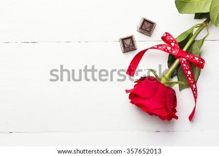 Hoa hồng, sôcôla trên nền gỗ màu trắng
