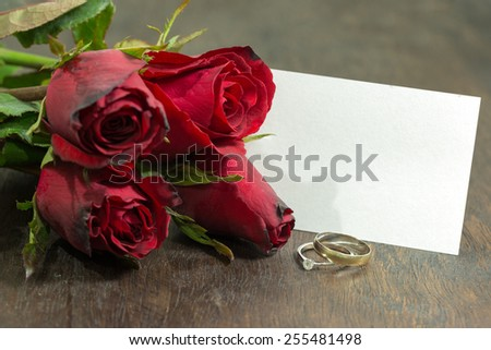 Red rose, diamond rings, and blank card - stock photo
