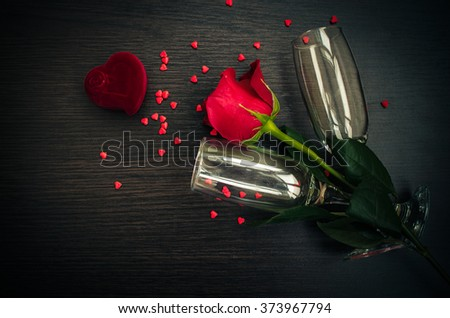 Red rose, engagement ring, hearts and champagne glasses over wood with copy space. Valentine's day background. Presents for woman on Valentine Day. love, proposal, relations, holidays concept. - stock photo