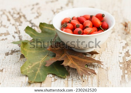 red rose hips in bowl with oak leaves on grunge wooden table - stock photo