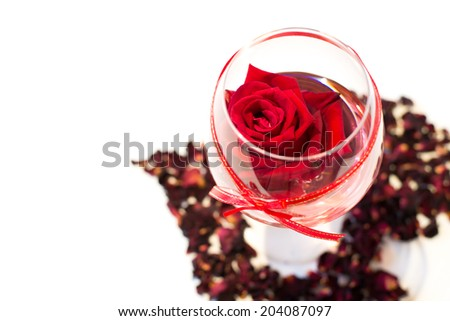 Red rose  in wine  glass with Heart made of rose petals isolated on white background