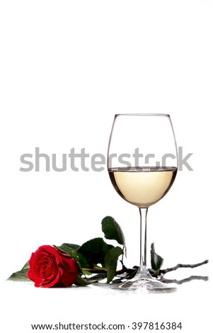 red rose next to a glass of white wine