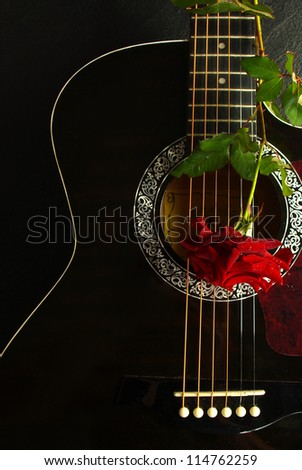 Red rose on a black acoustic guitar .Vertical.Can be used as a nice background, album cover. Dark colors, contrast