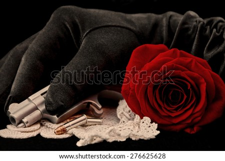Red Rose on white glove with handgun and bullets and hand in black glove on black velvet - stock photo