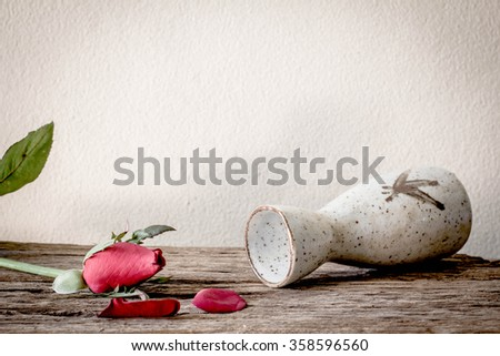Red rose on wooden table - stock photo