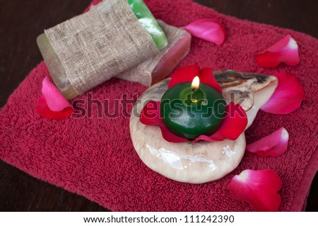 Red rose petals, candle, soap and towel - stock photo