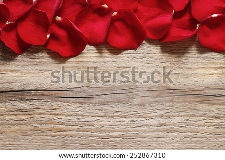 Red rose petals on wooden background - stock photo
