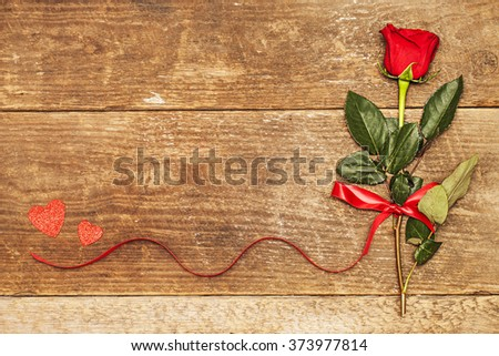 Red rose with bow and hearts on wooden board, Valentines Day