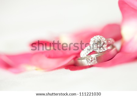 Red rose with diamond ring on white background - stock photo