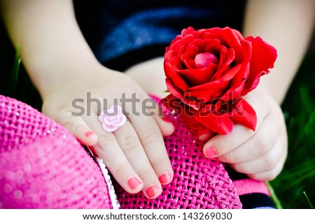 Red rose with little girl's hands outdoors - stock photo