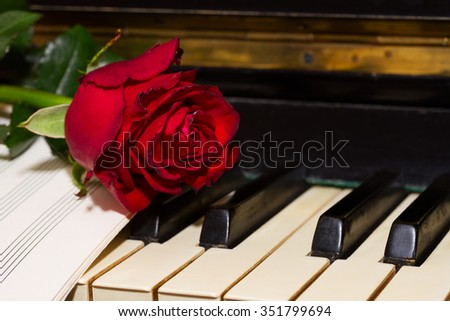 red rose with notes paper on vintage piano close up