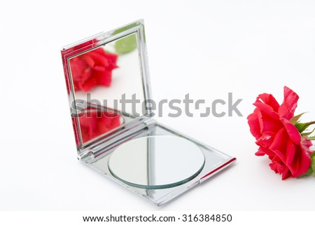 Red rose with open make up mirror with the reflections of a red rose - stock photo