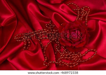 Red rose with red pearls are on red wrinkled satin.