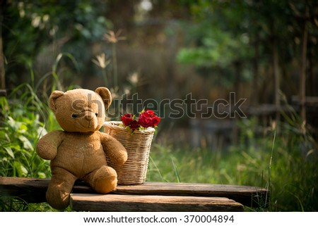 Red roses and a teddy bear on wooden background