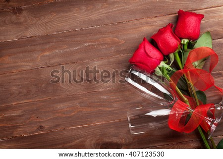 Red roses and champagne glasses over wood with copy space. Valentines day background - stock photo