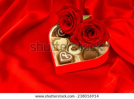red roses and chocolate pralines in golden heart shape gift box on satin background - stock photo
