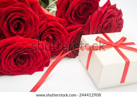 Red roses and gift box on white background - stock photo