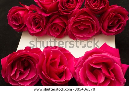 red roses and white card with a place for a congratulatory text on a black background