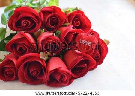 red roses bouquet with heart and letter love on white wood background for valentine mothers day