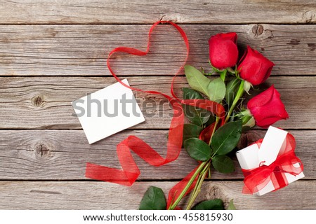 Red roses, gift box and heart shape ribbon over wooden table. Valentines day background. Top view with copy space - stock photo