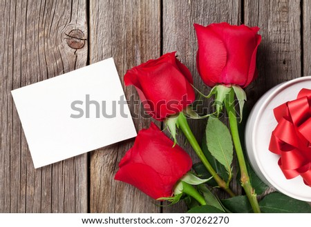 Red roses, gift box and Valentine's day greeting card. Top view with copy space - stock photo