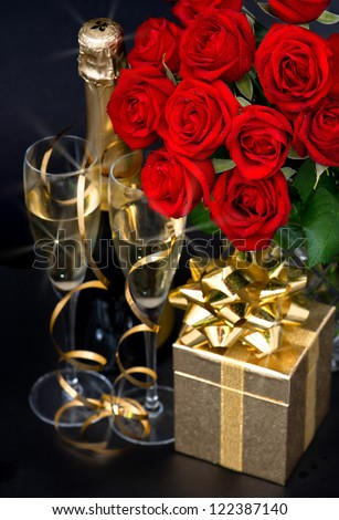 red roses, golden gift and and champagne on black background - stock photo