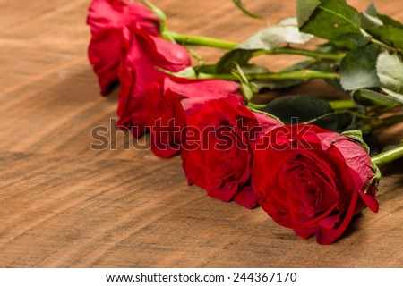 Red roses in a row on a wooden table - stock photo