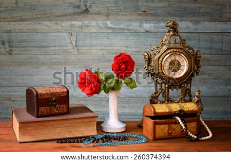 Red roses in a vase, clock and jewelry on the table - stock photo
