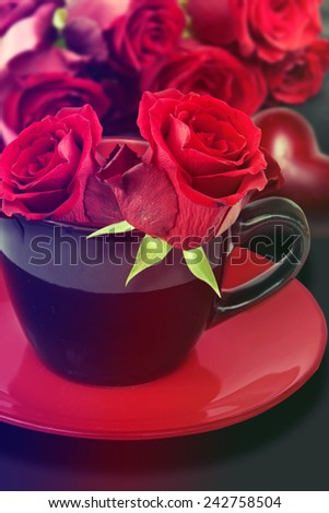 Red roses in the cup. Valentine's Day.