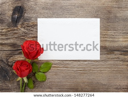 Red roses on wooden background. Blank sheet of paper. Copy space. - stock photo