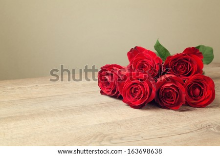 Red roses on wooden vintage table with copy space