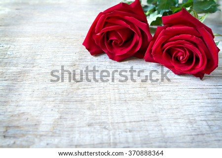 Red roses on woonden background. Valentine's Day, anniversary etc background. - stock photo