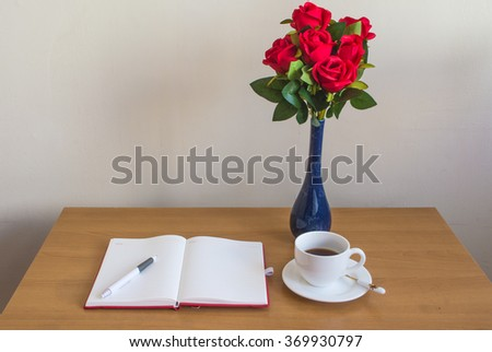 red roses,opened notebook, cup of coffee and pen on wooden office desk.