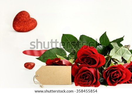 Red roses with an empty label and glitter hearts in the background. Room for copy space with extreme shallow depth of field. - stock photo