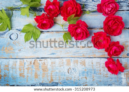 Red roses with green leaves on wooden background