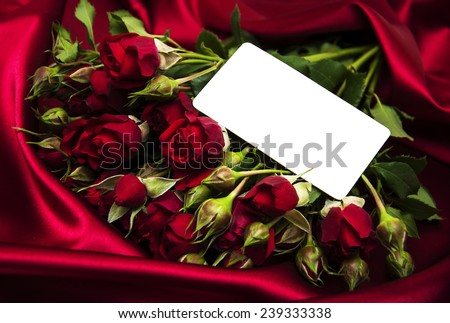 Red roses with greeting card on a silk  background