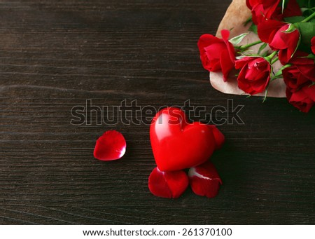 Red roses wrapped in paper with heart on wooden table background