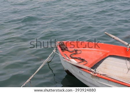Red rowing boat and oars on the water - stock photo