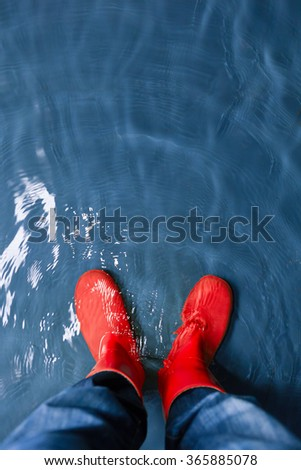 red rubber boots in the water - stock photo