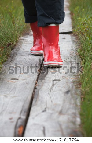 Red rubber boots on hiker hiking trail