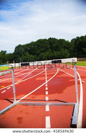 red running athletic track with hurdle, bad weather, wet - stock photo