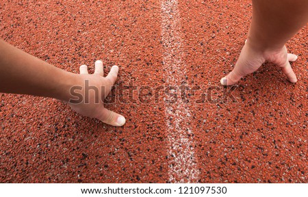 red running track field with white lines,a man's hand on ground ,start to run - stock photo