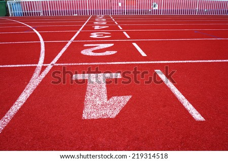 Red running track numbers one two three in stadium - stock photo