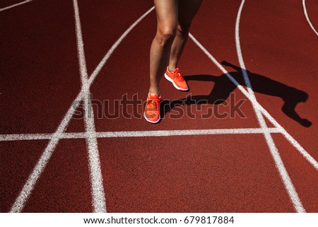 Red running track  with female runner, close up on legs
