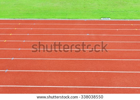 Red running tracks with green field at stadium - stock photo