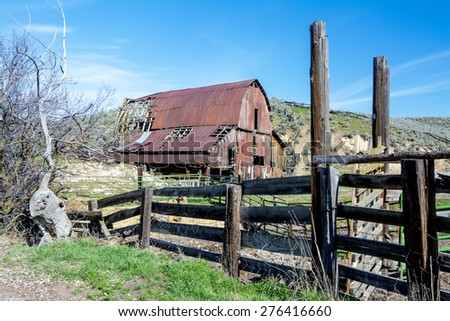 Red rusted barn and weathered corral - stock photo