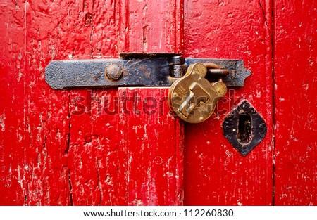 Red, rustic door with closed padlock - stock photo