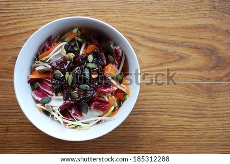 Red salad with carrots, sprouts, pumpkin seeds and seaweed in white bowl on wooden background, free space for text