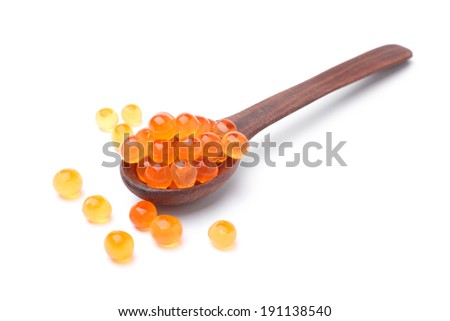 Red salted caviar with wooden spoon on white background - stock photo